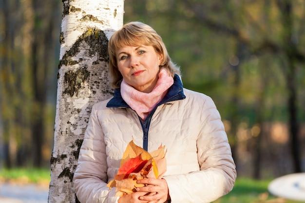 中年の女性が木々の間の秋の公園を歩く