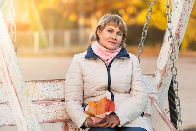 중년 여성은 나무 사이 가을 공원에서 산책