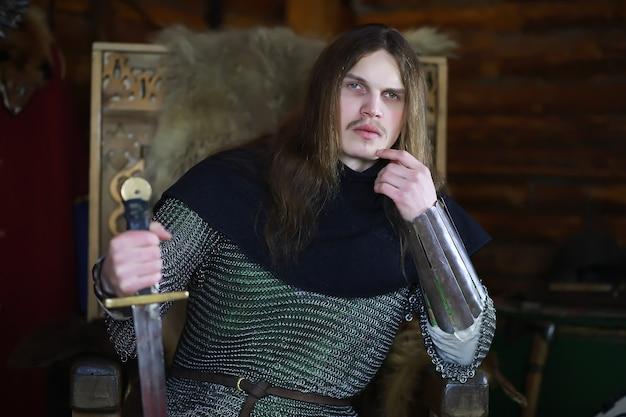 Могучий герой с длинными волосами в кольчугах в древнем зале. средневековый воин в рыцарских покоях.