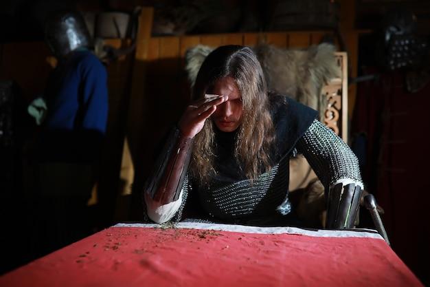 古代のホールの鎖帷子の鎧を着た長い髪の強大な英雄。騎士の部屋にいる中世の戦士。