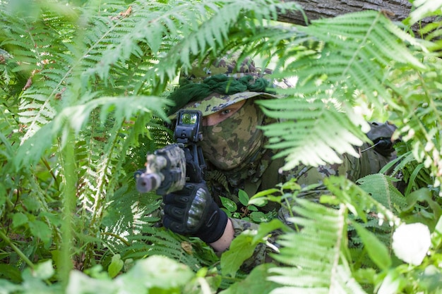 Военный в лесу сидит в засаде. солдатский пулемет и одежда