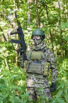 Военный в лесу с автоматом в мирное время. подготовка военных к боевым действиям.