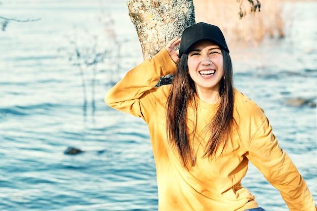Девушка-миллениал улыбается и позирует возле озера