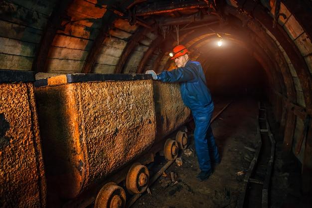 Шахтер в угольной шахте стоит возле тележки. копировать пространство