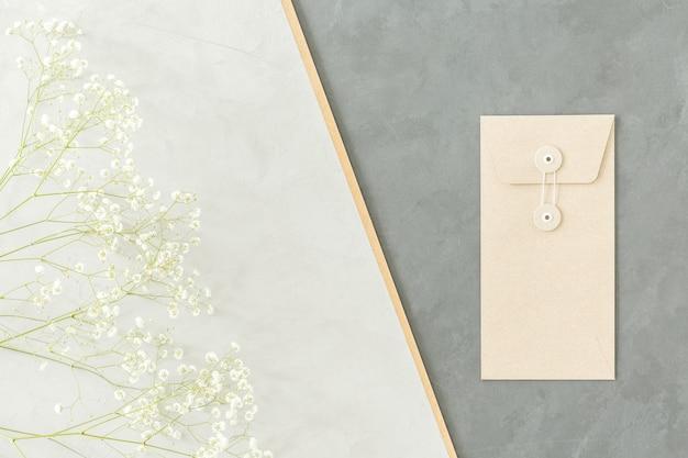 Минималистичная геометрическая композиция с маленькими белыми цветами и конвертом на светлом и темно-сером фоне.