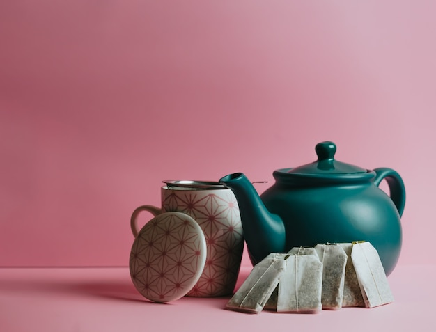 パステルピンクの背景にミニマルな青いティーポット、お茶、ファストティーの封筒