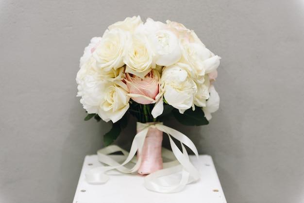 灰色の背景に分離されたティーテーブルの上に立っているミニマルなバラの花束
