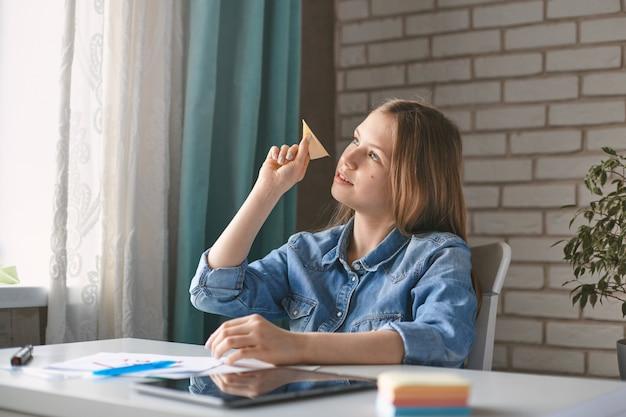いたずら好きな女子高生が紙飛行機を手に持ち、宿題をしながら休んでいる。