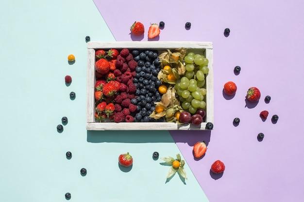 Смесь свежих ягод в деревянном ящике на ярко-зеленом и фиолетовом фоне. тропики. здоровое питание для диеты. витамины. вид сверху с копией пространства. горизонтальная ориентация.