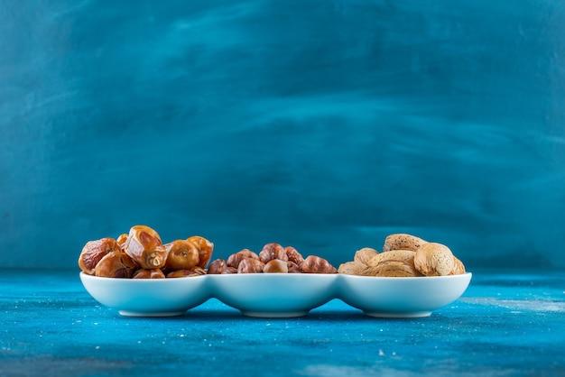 파란색 테이블에 그릇에 견과류의 혼합.