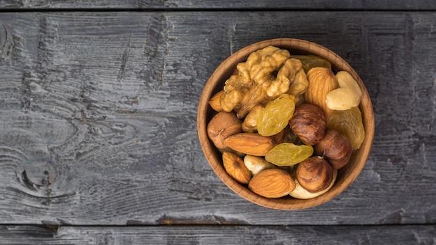 Смесь сухофруктов и различных орехов на деревянном столе. натуральная здоровая вегетарианская пища. плоская планировка.