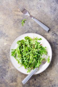 신선한 arugula, chard 및 mizun 잎을 접시에 넣고 포크를 테이블에 올립니다. 건강한 식생활. 상단 및 세로보기