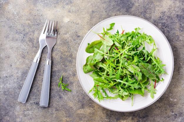 신선한 arugula, chard 및 mizun 잎을 접시에 넣고 포크를 테이블에 올립니다. 건강한 식생활. 평면도