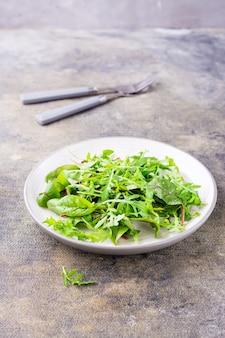 신선한 arugula, chard 및 mizun 잎을 접시에 넣고 포크를 테이블에 올립니다. 건강한 식생활. 세로보기