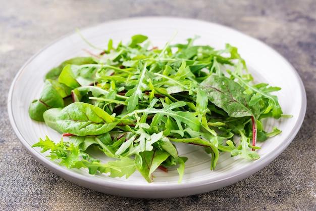 신선한 arugula, chard 및 mizun 잎의 혼합물을 테이블 위의 접시에 담습니다. 건강한 식생활. 확대