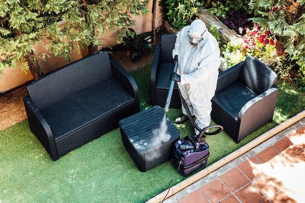 Мужчина в сиз дезинфицирует сад дома от коронавируса covid-19