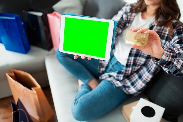 オンラインショッピングまたは宅配用のモバイルアプリケーション。タブレットpc画面と若い女性の手の中のクレジットカードのクローズアップ。グラフィックスとテキスト、クロマキーのための場所。