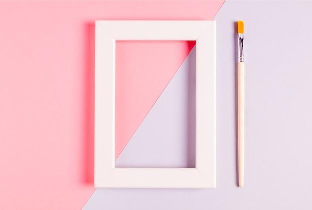 분홍색과 라일락 레이어에 흰색 빈 프레임과 장식 및 페인팅을위한 브러시의 모형. 미니멀리즘. 선택적 초점.