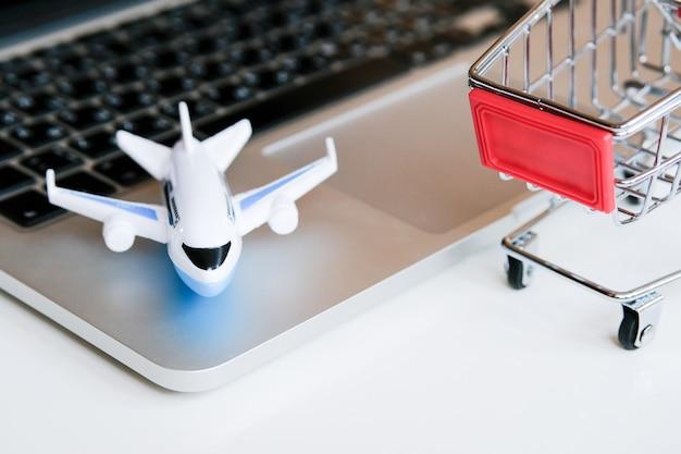 Модель самолета стоит на ноутбуке рядом с тележкой. покупка билетов на рейс через интернет.