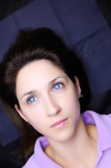 Девушка-модель с голубыми глазами лежит на процедуре перманентного макияжа, ее брови готовят к напылению пудры.