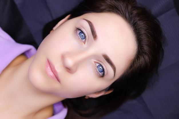 Девушка-модель с голубыми глазами лежит на косметологической кушетке с татуированными бровями