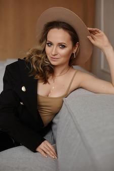 室内でポーズをとる流行の帽子をかぶった完璧なメイクと青い目をしたモデルの女の子