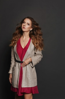 ピンクのドレスと黒の背景にポーズをとるモダンなトレンチコートを着た完璧なメイクと髪型のモデルの女の子