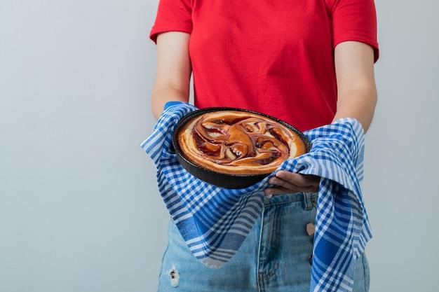 Модель держит сладкий пирог на черной сковороде
