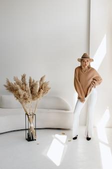 スタジオでスタイリッシュな秋のイメージの帽子をかぶったモデル。ブロガー