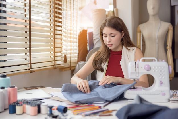 モデルは、ファッションデザイナーが新しいデザイナーの衣服を試すために使用します。職場では、ファブリックビジネスの女性起業家がファッションデザイナーのために新しい服をデザインしています。