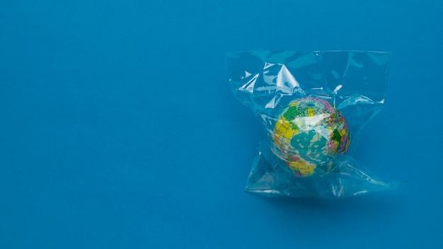 Модель земного шара в полиэтиленовом пакете на синем фоне. место для текста. плоская планировка.