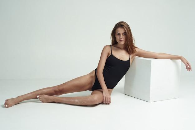 Модель с бронзовой кожей и витилиго сидит на белом полу. девушка в черном боди
