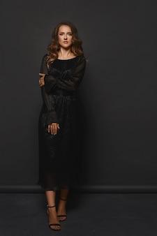 黒の背景にポーズをとって黒のイブニング ドレスを着たモデルの女性