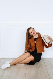 가벼운 모자 옆에 갈색 재킷을 입은 모델 여자. 쇼룸에서 의류 시연