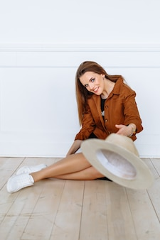 갈색 재킷을 입은 모델 여성이 가벼운 모자를 앞으로 던졌습니다. 쇼룸에서 의류 시연