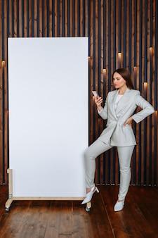 携帯電話を手に持つビジネススーツのモデルの女性が白いキャンバスを表示