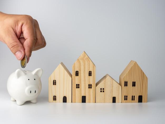 モデルの木造住宅とコインを持っている男の手。住宅事業のコンセプト。