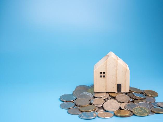 Модель деревянного дома и куча монет на синем