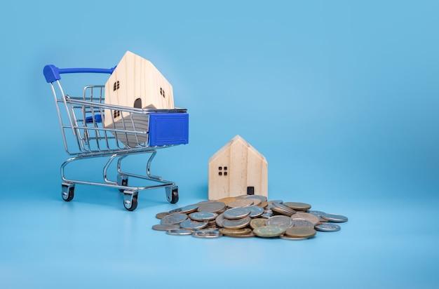 Модель деревянного дома на тележке для покупок с кучей монет на синем