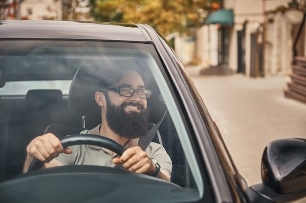 차를 운전하는 현대 수염 된 남자