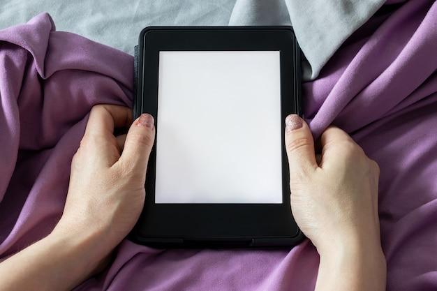 灰色と紫色のベッドの上の女性の手に空白の画面がある現代の黒い電子書籍リーダーの電子書籍。マイクロファイバー寝具のクローズアップのモックアップタブレット