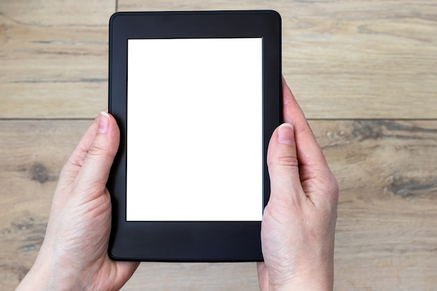 ぼやけた木製のタイル張りの床の背景に女性の手で白い空白の画面を持つ現代の黒い電子書籍。モックアップタブレットのクローズアップ
