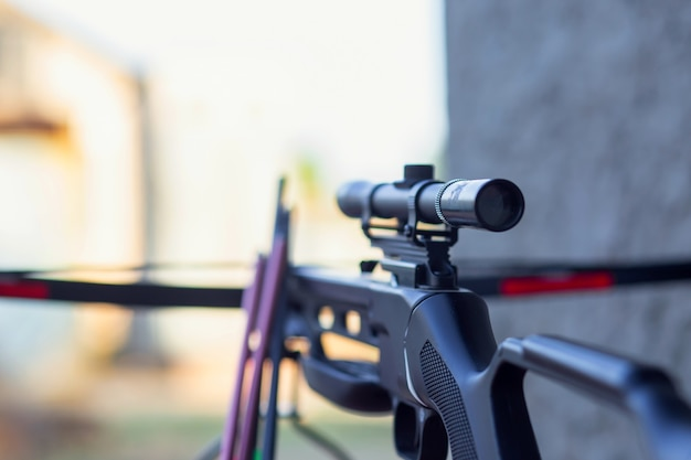 Современный арбалет со стрелами и оптическим прицелом лежит на деревянном столе на улице. подготовка к охоте.