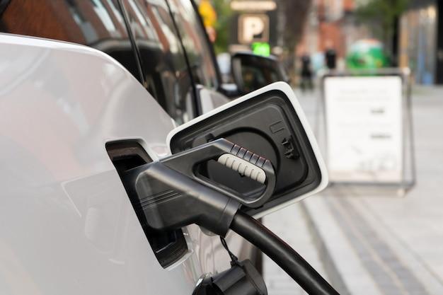 케이블로 전원 공급 장치에 연결된 현대적인 전기 자동차는 도시의 급속 충전소에서 배터리를 충전합니다