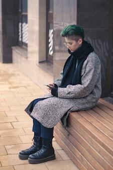 Осенью на городской улице современная девушка в повседневной одежде пользуется смартфоном. социальные сети, общение.