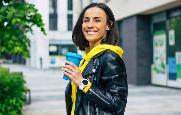 散歩中の現代の女の子!彼女の新しいかわいいスマートウォッチで、彼女の快適なサーマルマグで温かい飲み物を飲みながら、彼女の一日を楽しんでいる若い現代の女の子。