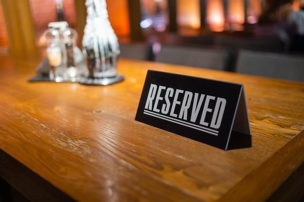 あなたの場所の予約の碑文と予約されたテーブルのための現代的なアイデア。アイデアレストランカフェの木製テーブルに予約された碑文。