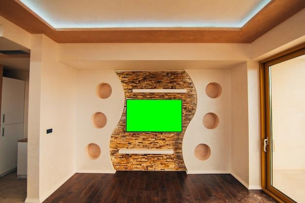 녹색 화면이 벽에 걸려있는 현대적인 lcd tv