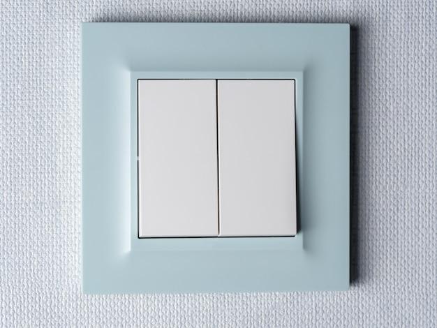 На стене крепится современный выключатель света с голубой каймой.