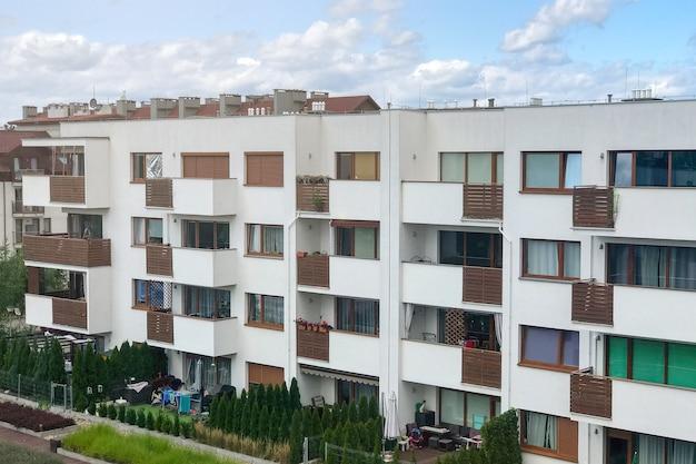Современный малоэтажный дом с небольшими балконами и большими окнами на фоне голубого неба.